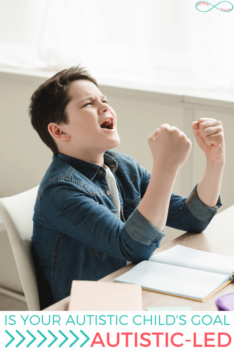 "Boy sits at a table in front of a journal. His face and hands show that he's excited (as if he's saying YES!) and text reads: ""Is your Autistic child's goal Autistic-led?"" There's a teal and coral Autistic Mama infinity sign logo in the top right corner."