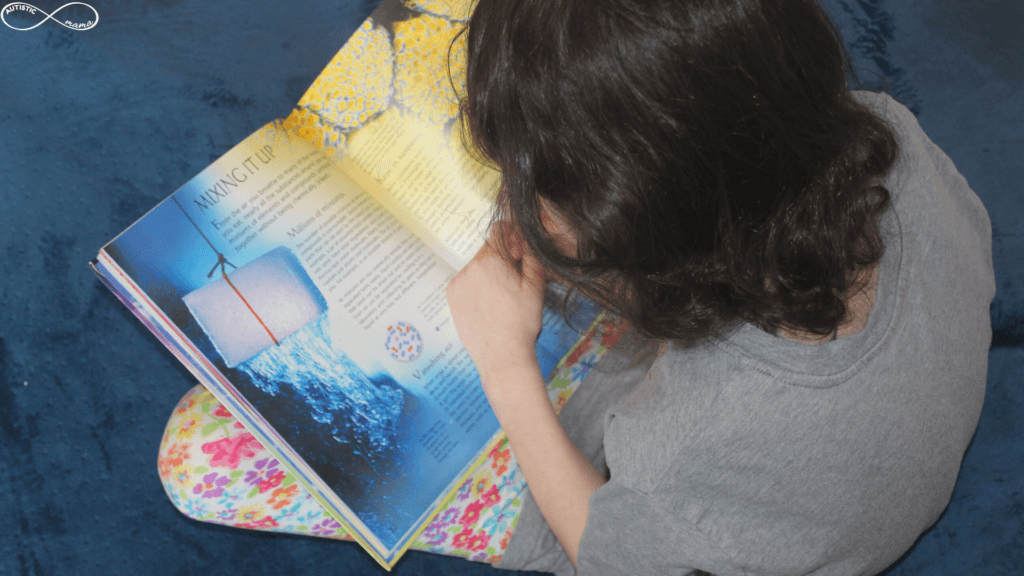 """Mr. C sitting cross-legged on our crash pad reading a colorful page from a science book. The page is titled """"Mixing it Up"""""""