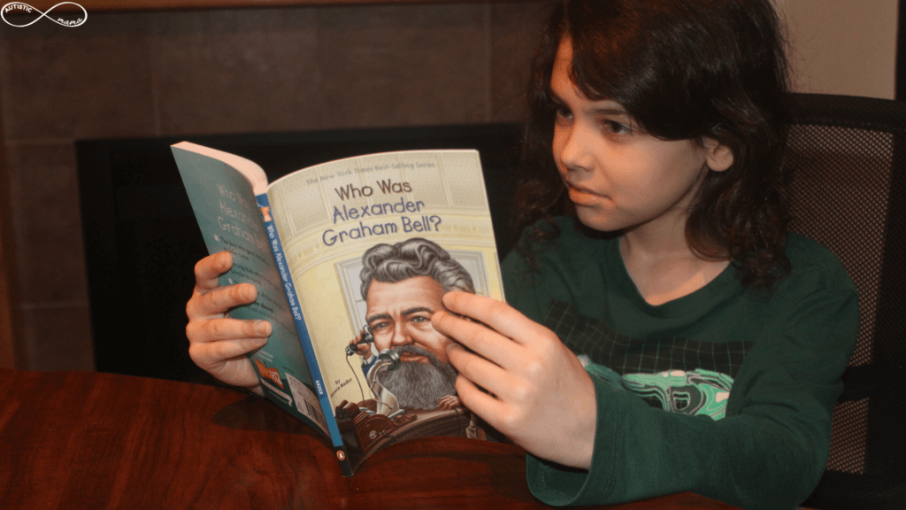 "Image of Mr. C sitting at a table wearing a green shirt and reading the book ""Who Was Alexander Graham Bell"""