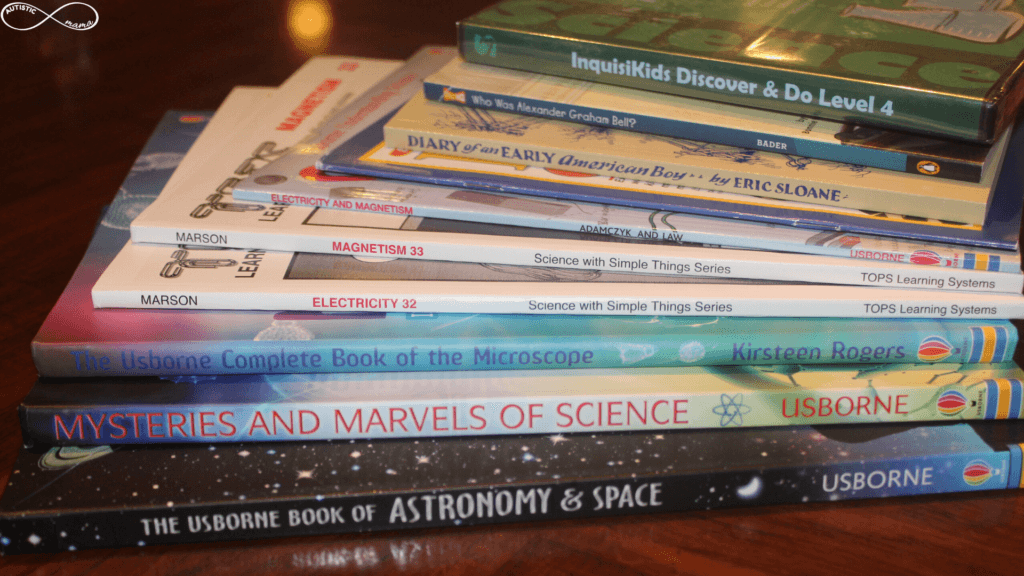 Stack of books on a table including: The Usborne Book of Astronomy & Space, Mysteries and Marvels of Science, The Usborne Complete Book of the Microscope, Science With Simple Things Electricty 32, Science With Simple Things Magnetism 33, Electricity and Magnetism, Diary of an Early American Boy, Who Was Alexander Graham Bell, and the DVD Inquisikids Discover & Do Level 4