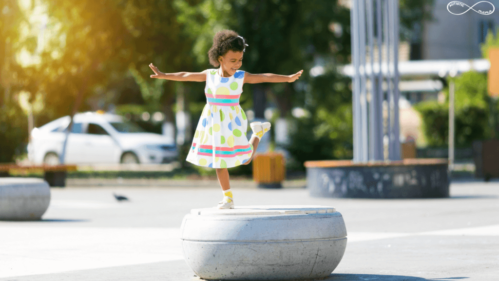 Black little girl wearing a bright polka dot dress stands on one foot with her arms out for balance on a structure in a park.
