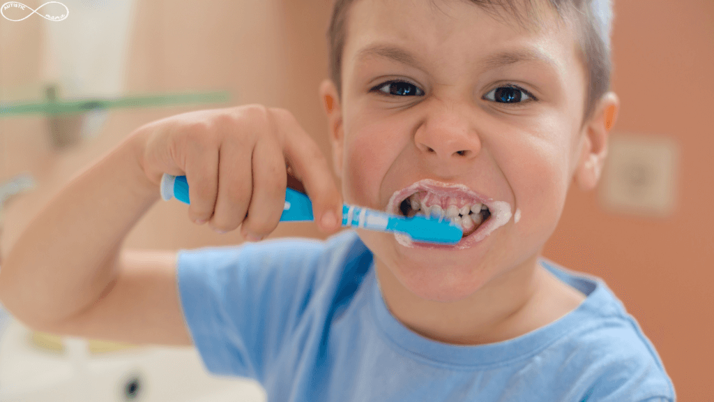 Young white boy holding a blue toothbrush and brushing his teeth.